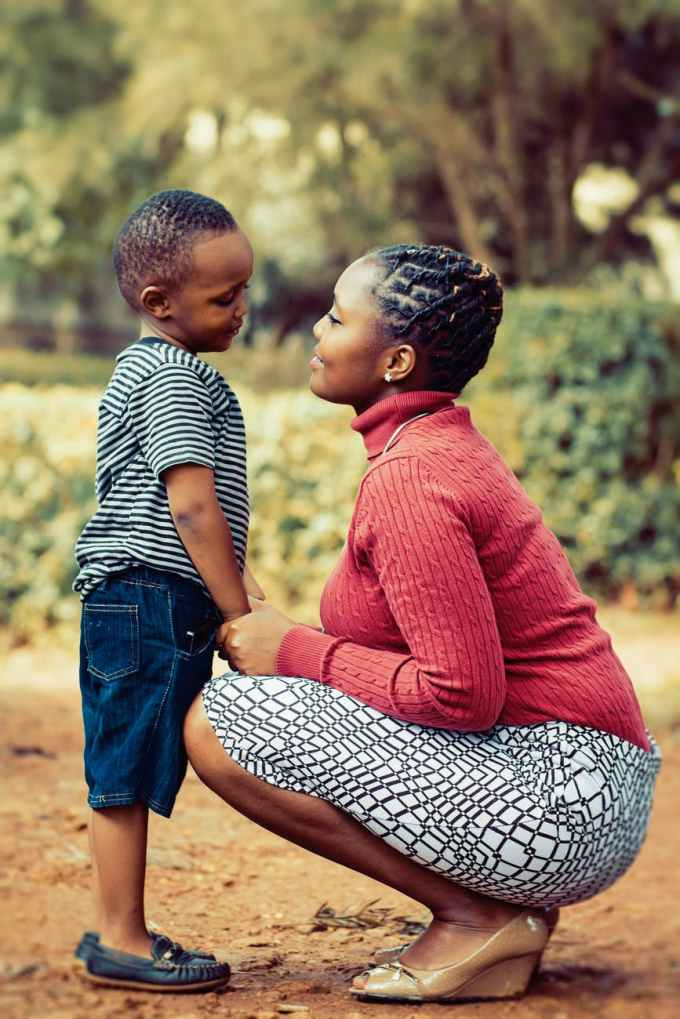 tilt shift lens photography of woman wearing red sweater and white skirt while holding a boy wearing white and black crew neck shirt and blue denim short