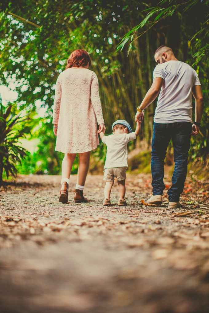 low angle shot of a child held by woman and man on on each hand walking on an unpaved pathway outdoors