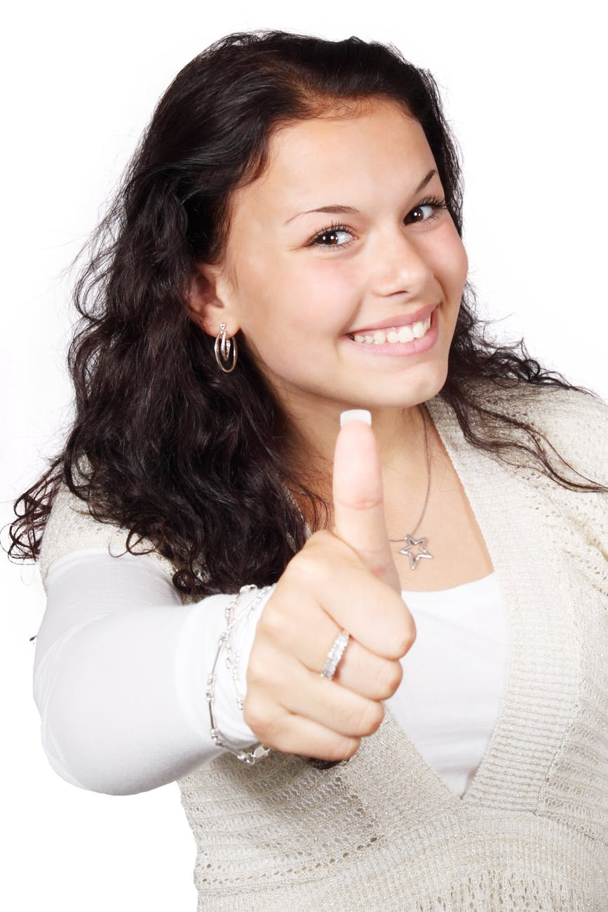 smiling woman wearing white and beige showing thumbs up