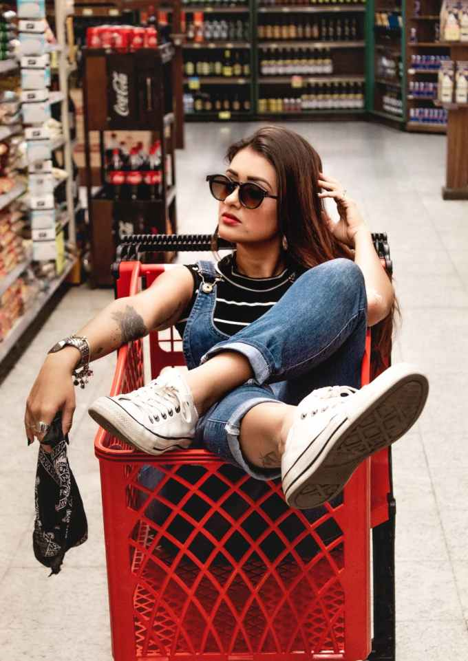 woman wearing blue jeans riding red shopping cart