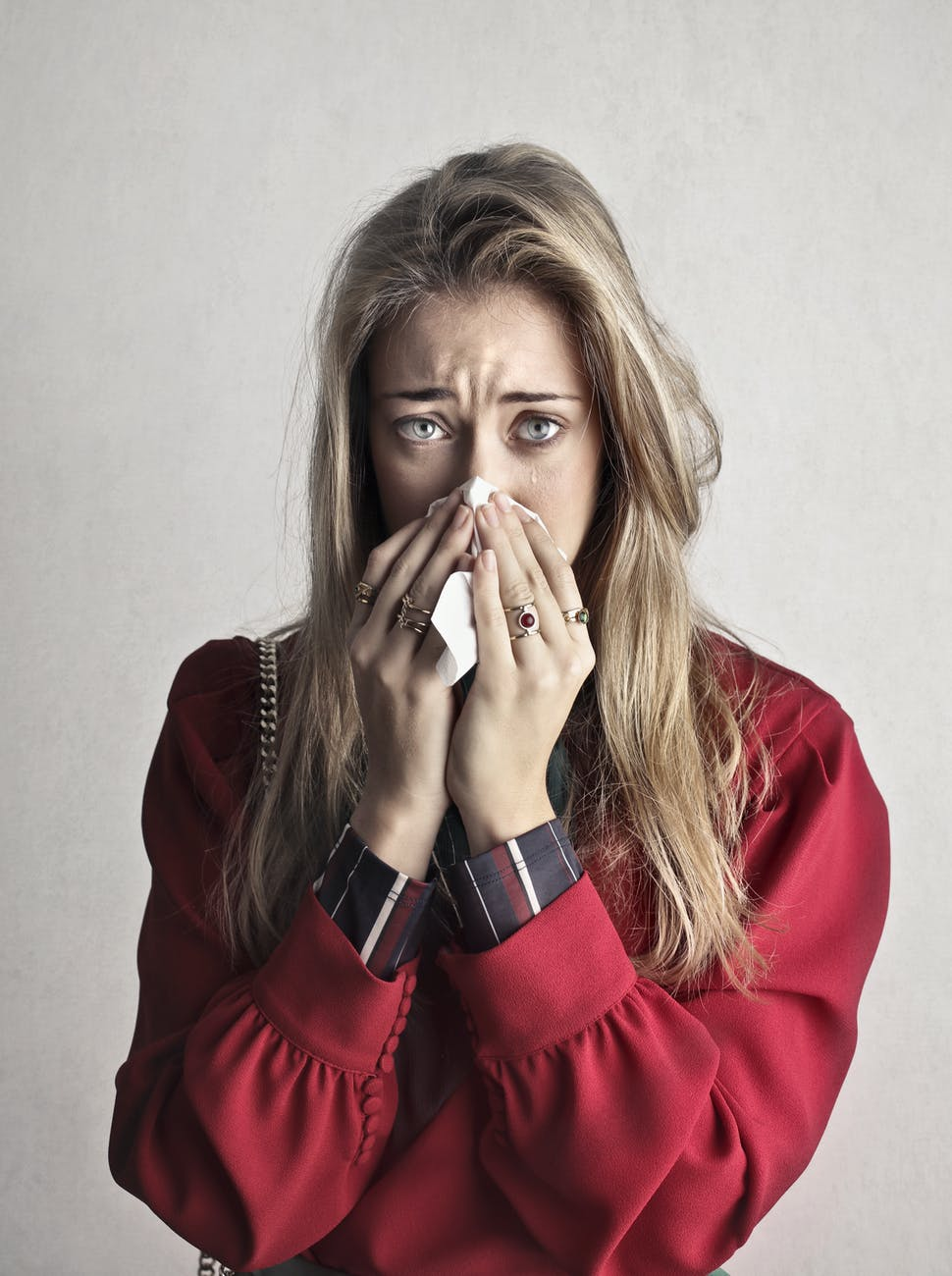 photo of crying woman in red long sleeve shirt blowing her nose