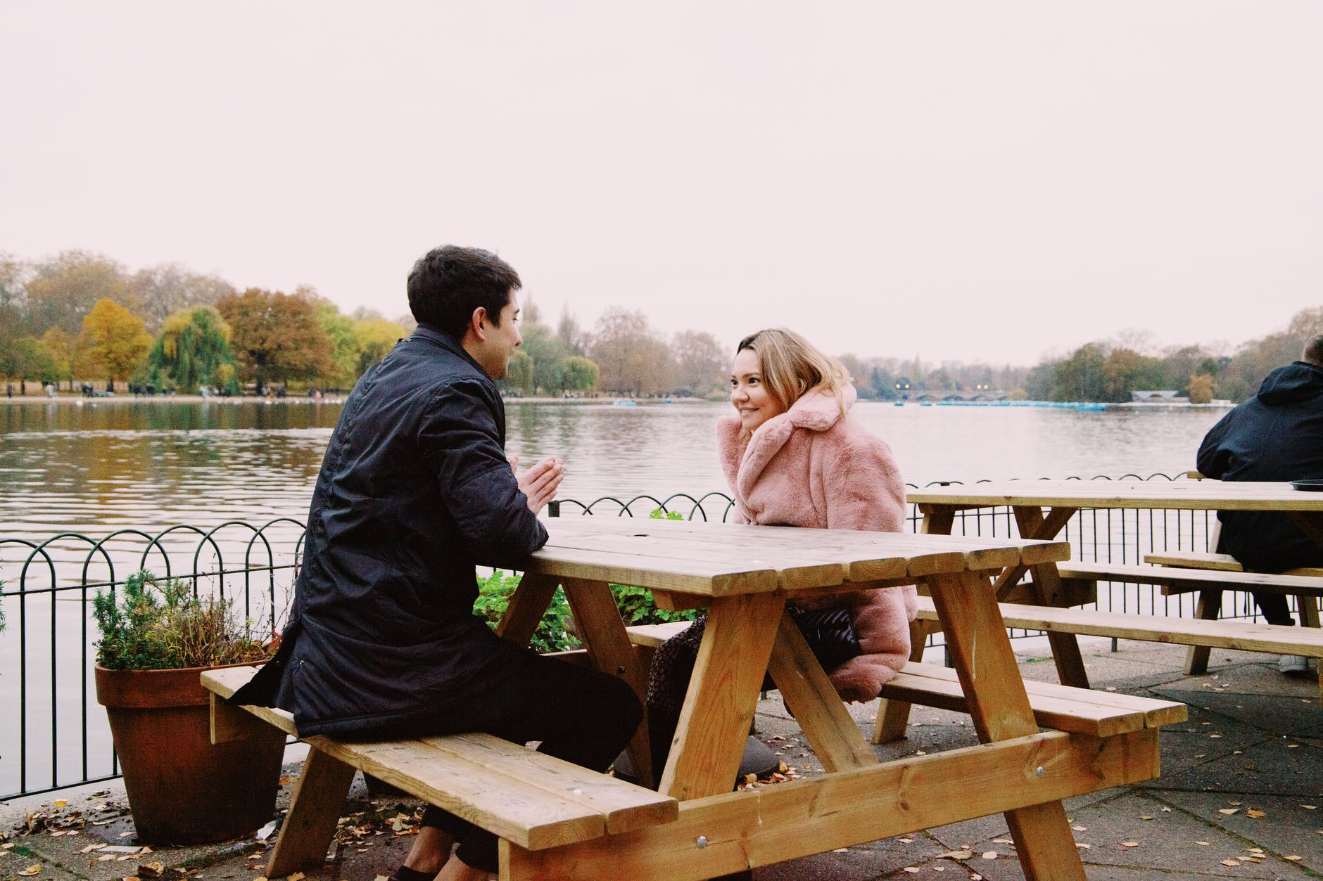cheerful young couple resting in cafe at lakeside during romantic date on autumn day