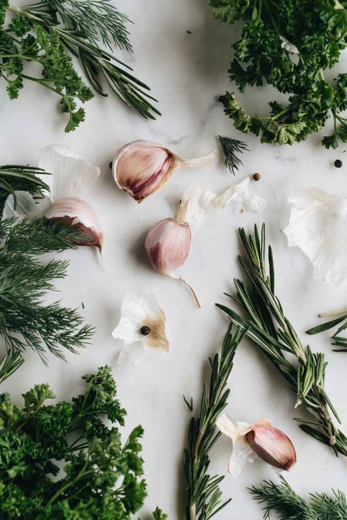close up photo of garlic near herbs