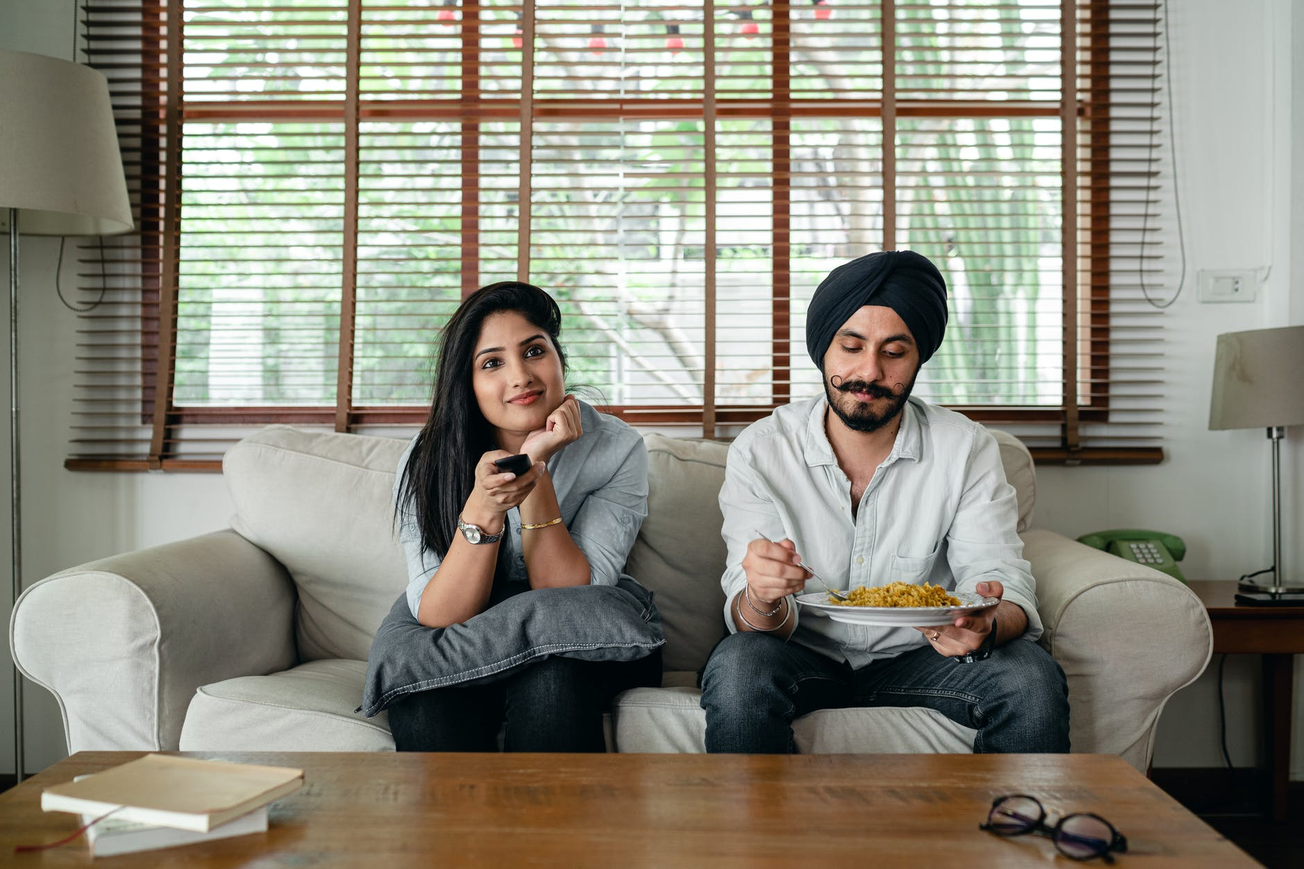 calm ethnic couple watching movie on sofa