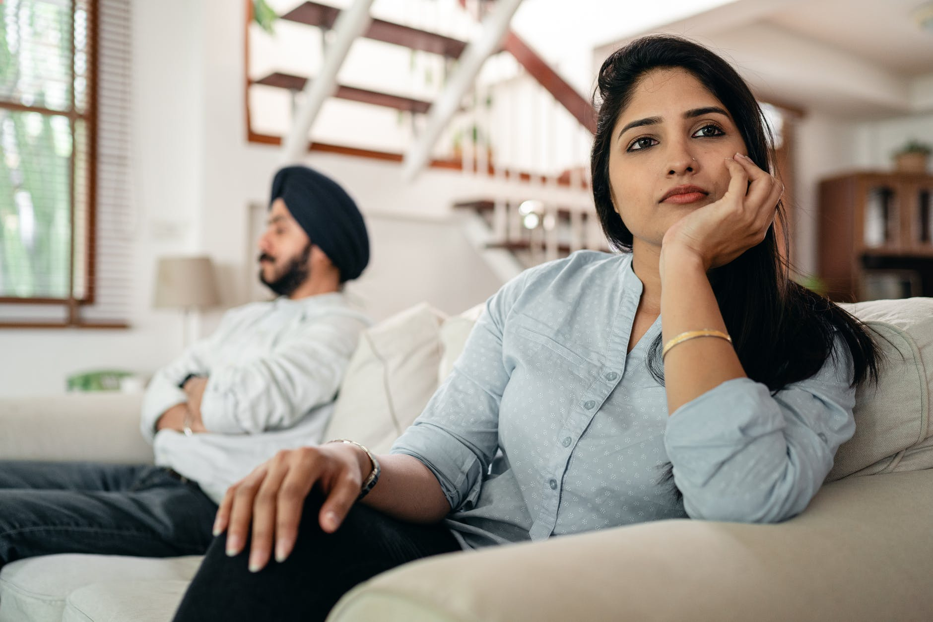 sad young indian woman avoiding talking to husband while sitting on sofa