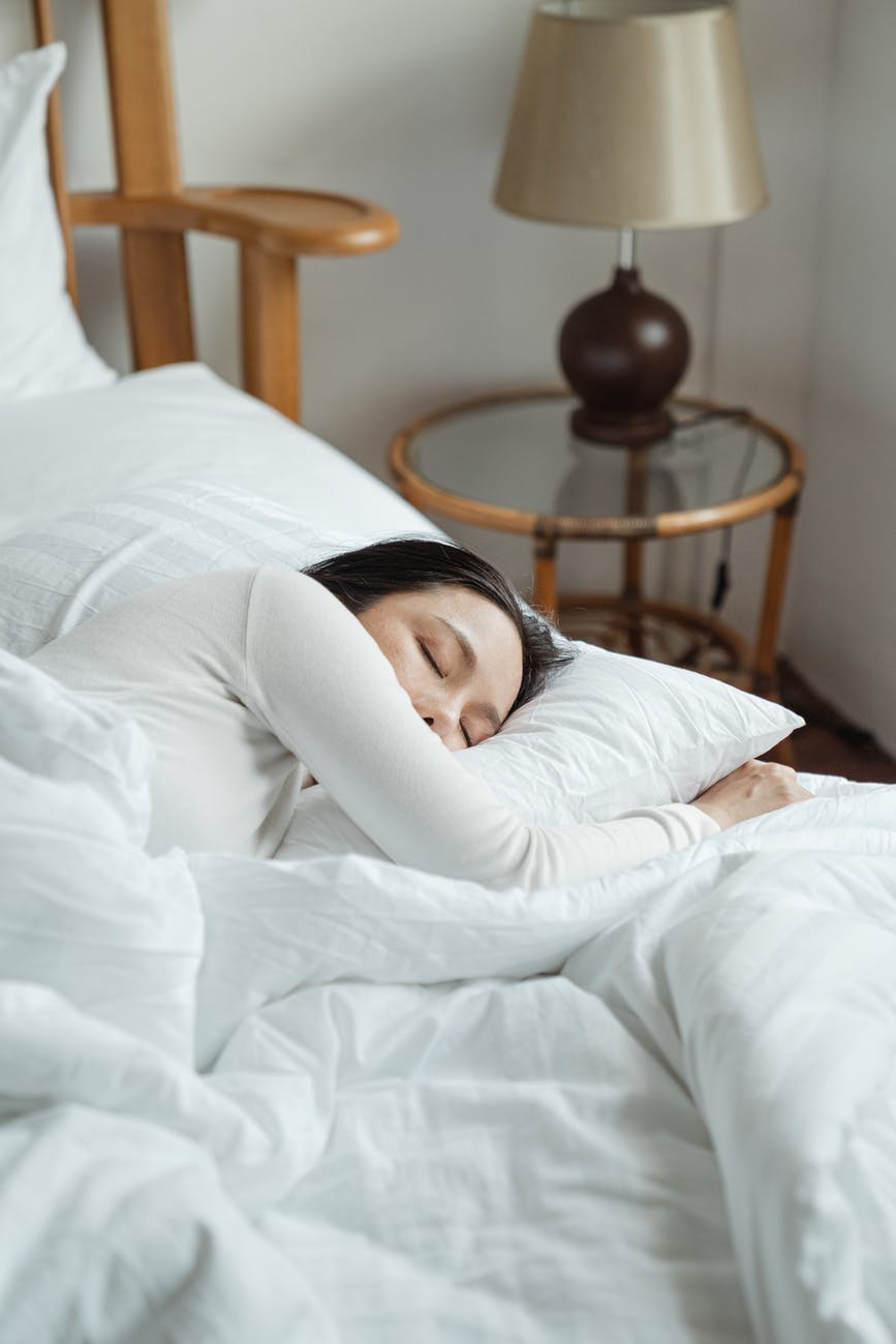 young woman sleeping in comfy bed