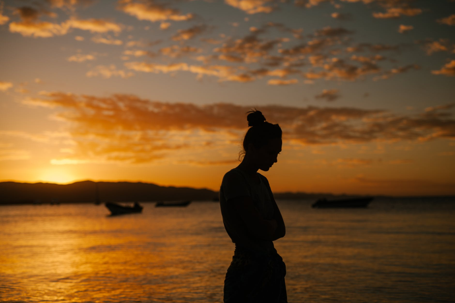 sad woman standing on coast of sea at sunset