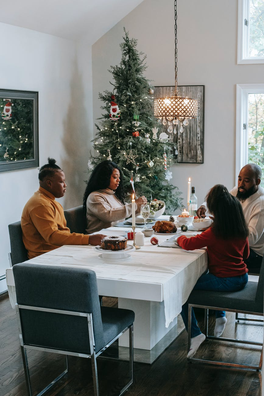 black family celebrating christmas at served table at home