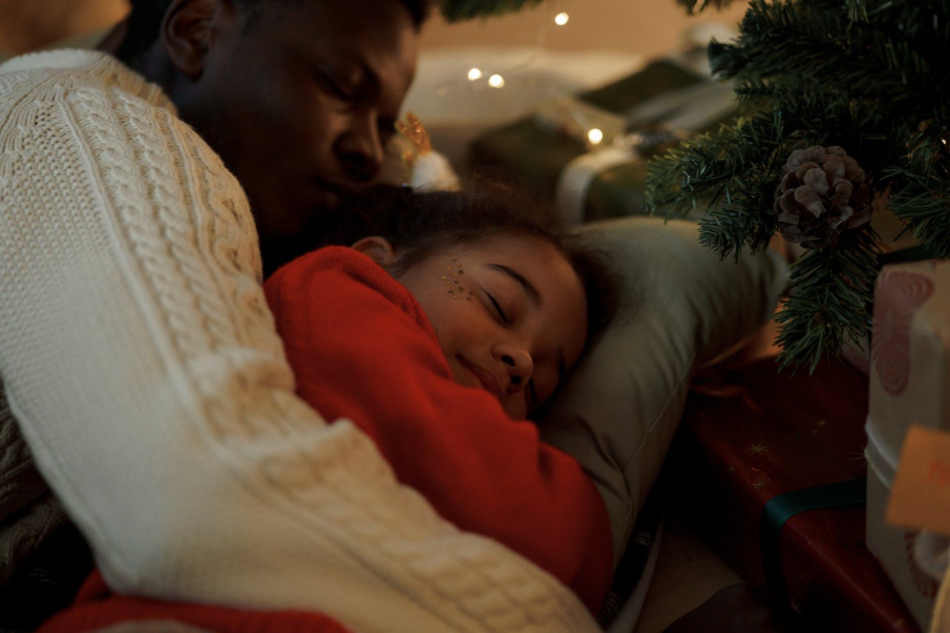 dad embracing her daughter while sleeping